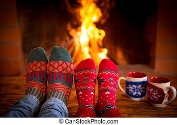 Couple near fireplace - Couple relaxing at home. Feet in...