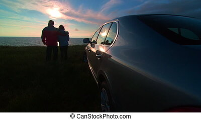 Couple near his car enjoying view of the sea coast at sunset