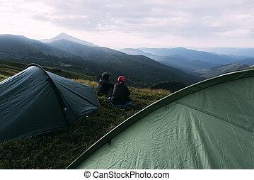 Couple near tent on mountains closeup