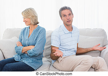 Couple not taking after a fight and man looking confused at camera at home on couch