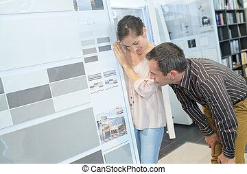couple of adults choosing ceramic tile for bathroom