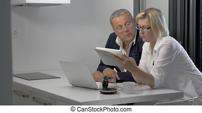 Couple of adults with pad in kitchen