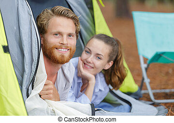 couple of backpackers sitting outside the tent