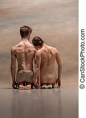 Couple of ballet dancers posing over gray background. . Back...