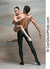 Couple of ballet dancers posing over gray background.