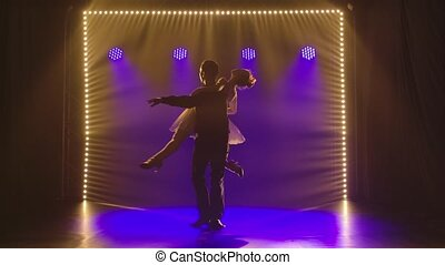 Couple of ballroom dancers are dancing romantically in a dark studio against the backdrop of bright blue lights. Silhouettes of man and woman dancing elements of rumba, salsa or flamenco. Slow motion