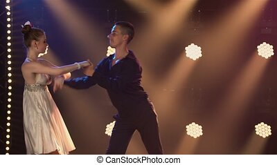 Couple of ballroom dancers are dancing romantically in dark studio against backdrop of bright lights. Man in a black suit and woman in white dress dance elements of rumba, salsa or flamenco. Close up