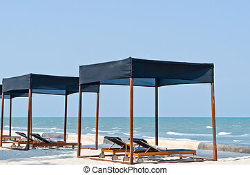 Couple of beach tent with lounge chairs