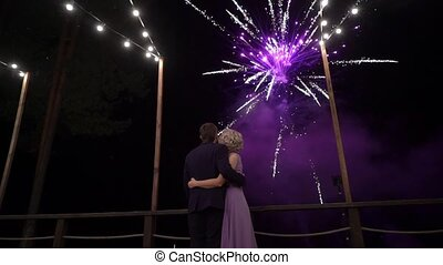 Couple of beautiful stylish newlyweds looking at fireworks...