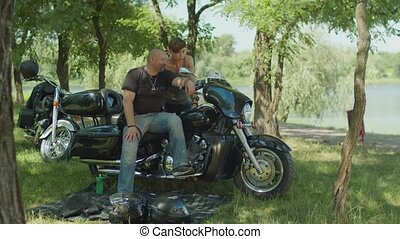 Couple of bikers discussing motorbike in nature - Handsome...
