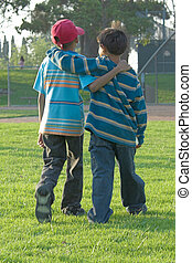 two young boys walking with arms around back