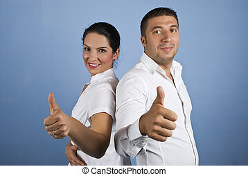 Couple of business people giving thumbs up