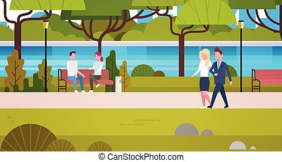 Couple Of Business People Outdoors Walking In Public Urban Park Relaxing