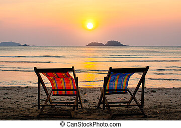Couple of chairs on sunset beach.