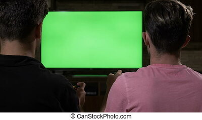 Couple of chilling focused guys on sofa playing video game with joypads on chroma key green TV screen