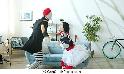 Couple of crazy mimes having fun dancing enjoying music indoors at home