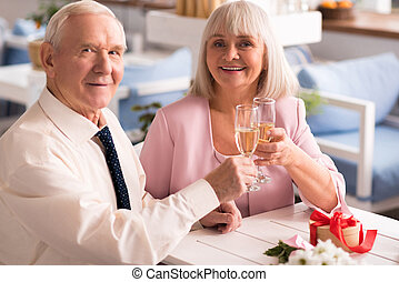 Couple of cute elderly people drinking champagne - It might...