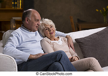 Couple of elderly people sitting on the couch in the living...