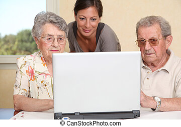 Couple of elderly persons with young woman using internet