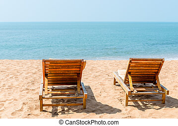 couple of empty chairs on a sandy beach in the afternoon