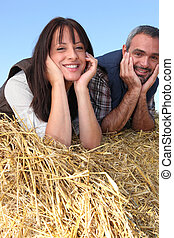 couple of farmers relaxing on a strawbale