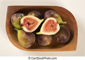 couple of figs in a pot over a white background.
