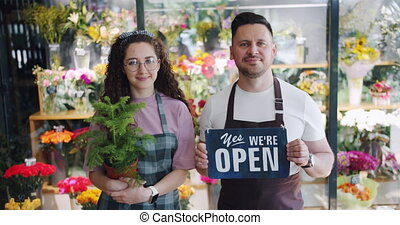 Couple of florists holding open slate and green plant...