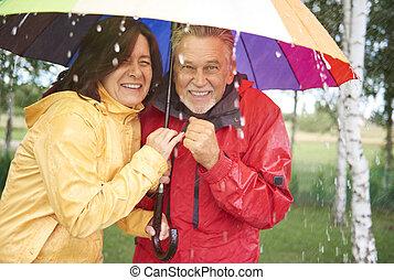 Couple of friend hiding under umbrella