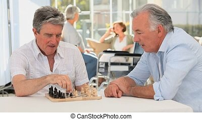 Couple of friends playing chess while their wifes are talking