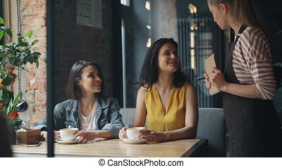 Couple of girls talking to waitress in cafe making order smiling chatting