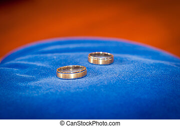 Couple of gold wedding rings on blue