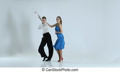 Couple of graceful dancers perform latino on white background, shadow