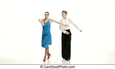 Couple of graceful dancers perform salsa on white studio...