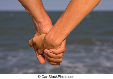 Couple of hands against the sea view