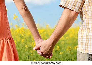 Couple of hands holding tight  in a beautiful yellow field