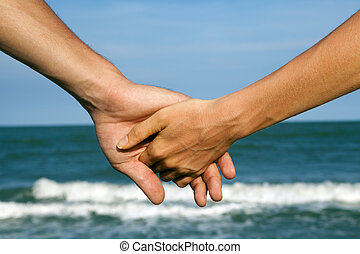 Couple of hands on the sea view