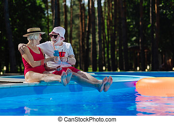 Couple of happy funny pensioners drinking cocktails near pool