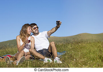 Couple of hikers making selfie with a retro camera  while on hiking