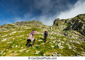 Couple of hikers on a trail in the mountains