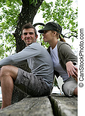 Couple of hikers sitting on a table outdoors