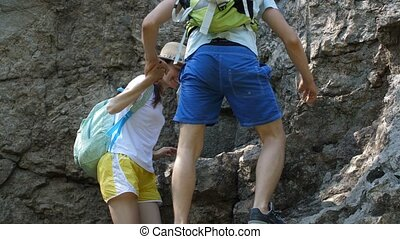 Travellers couple with backpacks climbing steep rocky terrain, helping each other to reach mountain peak during summer hiking. Positive hikers exploring wild nature during trek in rocky mountains.