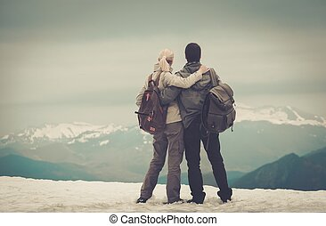 Couple of hikers with backpacks looking over mountains view