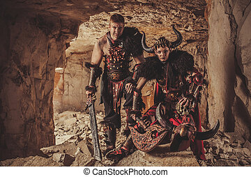 Couple of knights in armor with sword and axe. Catacombs on the background.