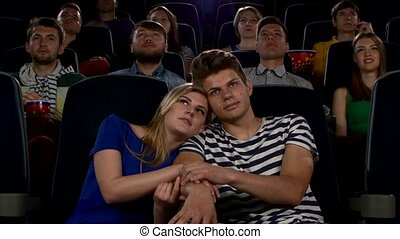 Couple of lovers in the front row watching a movie at the cinema