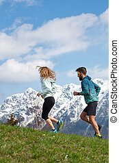 Couple of male and female athletes train in the mountains