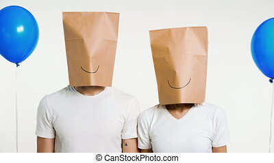 Couple of man and woman with smiley paper bag on the head ...