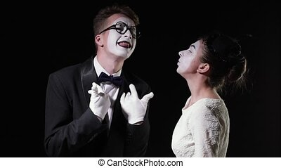couple of mimes talking to each other on black background