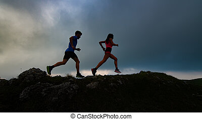 Couple of mountain runners man and woman train at sunset on a rocky ridge