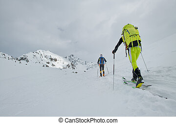 Couple of mountaineers with skis during a trip