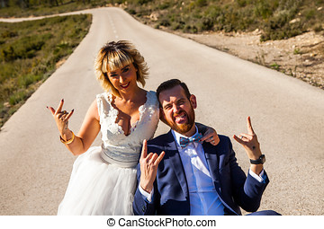 Couple of newlyweds pose in the middle of a lonely road making the horn gesture with their hands.